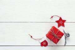 Den röda gåvaasken med garnering och sörjer kotten på en vit träflik Fotografering för Bildbyråer