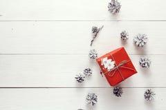 Den röda gåvaasken med garnering och sörjer kotten på en vit träflik arkivbild