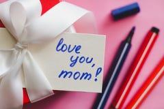 Den röda gåvaasken som binds med ett vitt band, markörer och ett kort med en inskrift 'älskar dig, mamma! 'på en rosa bakgrund royaltyfri bild