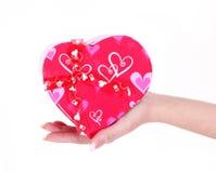 Den röda gåvan boxas i hjärta formar för valentin dag räcker in isolerat Arkivbild