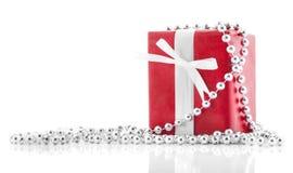 Den röda gåvan boxas med vitbandet som isoleras på vitbakgrund Semestrar begrepp Royaltyfri Foto