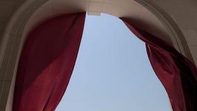 Den röda gardinen i bågen framkallar i vinden långsam rörelse stock video