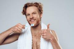 Den röda haired le mannen borstar tänder royaltyfria bilder
