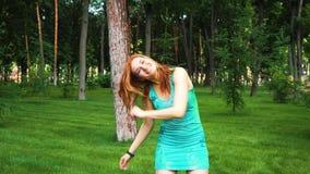 Den röda haired unga kvinnan i våta klänning- och Holi målarfärgskratt och hopp parkerar in stock video