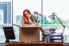 Den röda head kvinnan som flyttar sig till det nya kontoret som packar hennes tillhörigheter Arkivbild