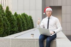 Den röda head mannen i den santa hatten, att arbeta som är utomhus-, tummar upp och se kameran Arkivbild