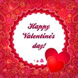 Den röda hjärtarundan inramar kortet för valentindaghälsningen Arkivfoto