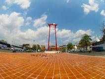 Den röda jätte- gungan är en religiös struktur i Phra Nakhon med den färgrika blommaträdgården i dag för molnig himmel arkivfoto