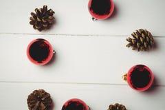 Den röda julstruntsaken och sörjer kotten på trätabellen Arkivfoto