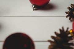 Den röda julstruntsaken och sörjer kotten på trätabellen Arkivbilder
