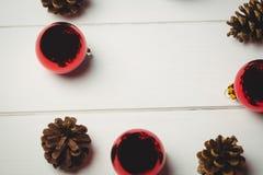 Den röda julstruntsaken och sörjer kotten på trätabellen Royaltyfri Bild