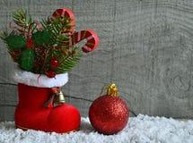 Den röda kängan för jultomten` s med granträdfilialen, dekorativa järnekbärsidor, godisrottingen och röd jul klumpa ihop sig Arkivfoto