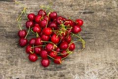 Den röda körsbäret bär frukt på träbakgrund Royaltyfri Fotografi