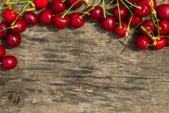 Den röda körsbäret bär frukt på träbakgrund Arkivbild