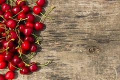 Den röda körsbäret bär frukt på träbakgrund Arkivbilder
