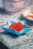 Röd kaviar i liten sjöstjärna formad bunke fotografering för bildbyråer