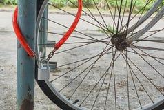 Den röda kedjan och silver färgade låset på cykelhjulet Arkivbilder