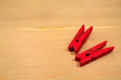 Den röda klädnypan som två förläggas på en trätabell Royaltyfri Foto