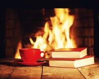 Den röda kopp te eller kaffe och gamla böcker near spisen Arkivbilder