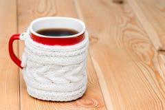 Den röda koppen i vit stack tröjan med varmt te Royaltyfri Fotografi