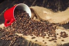 Den röda koppen med kaffebönor spridde på trätabellen Arkivfoto