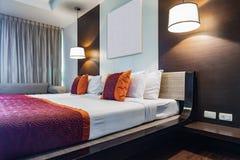 Den röda kudden på dubbelt sovrum med den vita bedsheeten och lampan tänder Fotografering för Bildbyråer