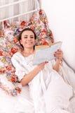Den röda kvinnan bokar i en säng Royaltyfria Foton