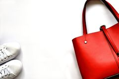 Den röda kvinnlign piskar handväskan och vita gymnastikskor royaltyfri bild