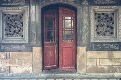 Den röda lantliga dörren på den tillbaka lantliga väggen Royaltyfri Foto