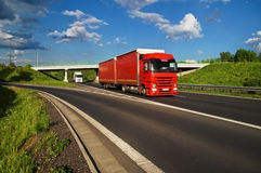 Den röda lastbilen som kör ner huvudvägen, under bron i bakgrunden, går den vita lastbilen Arkivfoto