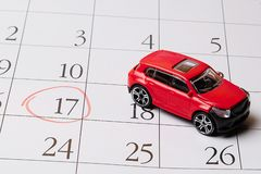 Den röda leksakbilen lokaliseras på kalendern, numret 17 cirklas i rött royaltyfri foto