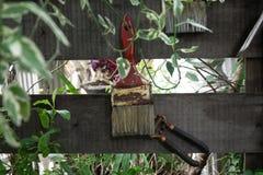 Den röda målarfärgborsten hänger dekorativt på staketet royaltyfri fotografi