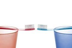 Den röda och blåa tandborsten på plasten- kuper mitt emot de på en vit bakgrund Royaltyfri Bild