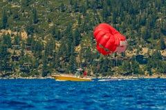 Den röda parasailvingen drog vid ett fartyg på Lake Tahoe i Kalifornien, USA arkivfoto