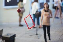 Den röda ramen väger, det hängda röda äpplet f?r grafittigata f?r konst f?rgrik r?knad v?gg arkivbilder