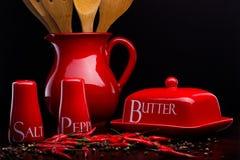 Den röda salt-källaren, peppar-asken, smör och kannan ställde in på mörk bakgrund av Cristina Arpentina Royaltyfria Foton