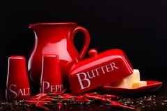 Den röda salt-källaren, peppar-asken, smör och kannan ställde in på mörk bakgrund av Cristina Arpentina Royaltyfri Foto