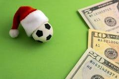 Den röda Santa Claus hatten kläs på en souvenirfotbollboll bredvid dollarna på en grön bakgrund Slå vad för julsportar royaltyfria foton