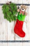Den röda Santas hatten, Teddy Bear och gräsplan sörjer trädfilialen royaltyfri bild