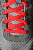 Den röda skon snör åt på rinnande skor Royaltyfri Fotografi