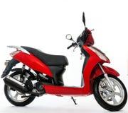 Den röda sparkcykeln står på en vit bakgrund royaltyfri foto