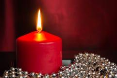 Den röda stearinljuset med en dekor från silver klumpa ihop sig Arkivbild