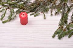 Den röda stearinljuset med sörjer träbakgrund för filial en, jul december Arkivbild
