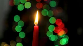 Den röda stearinljuset på en mörk bakgrund, julljus på bokeh tänder bakgrund, julaftonen, det nya året, xmas som färgas lager videofilmer
