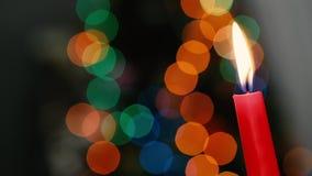 Den röda stearinljuset på en mörk bakgrund, julljus på bokeh tänder bakgrund, julaftonen, det nya året, xmas som färgas arkivfilmer