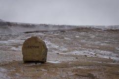 Den röda stenen med en inskrift GEYSIR står på varm jord i dalen av geysers i Island royaltyfri foto