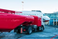 Den röda tankfartyget som tankar flygplanet som parkeras till en logibro på flygplatsförklädet Royaltyfri Foto