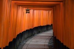 Den röda toriien utfärda utegångsförbud för gångbanabanan på relikskrin för fushimiinaritaishaen Royaltyfri Foto