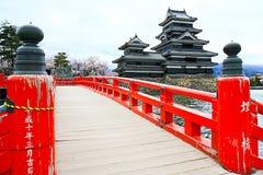 Den röda träbron och Matsumoto slotten Royaltyfri Foto