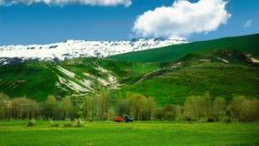Den röda traktoren fungerar i de första dagarna av våren på östliga Anatolien, Turkiet Arkivfoto